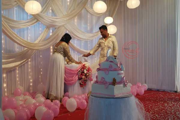 parents with baby in pink theme decor -Birthdays and Baptism planning by Red Carpet Events at pala kottayam kerala India Wedding Planning Gallery