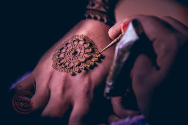 mehndi artist at work for the bride -Destination wedding by Red Carpet Events at punnamada resort alappuzha kerala India Wedding Planning Gallery
