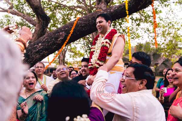 iyer ritual lifting the groom for varmala